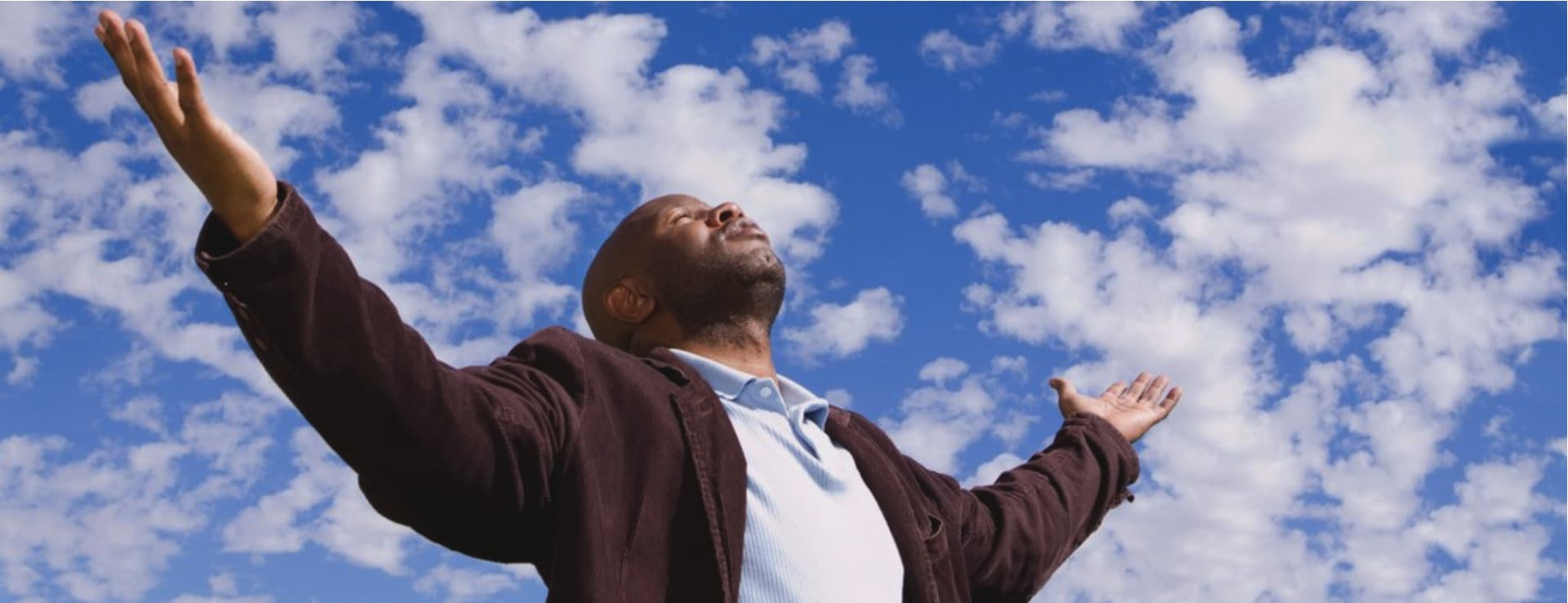 man with arms wide open looking up the sky