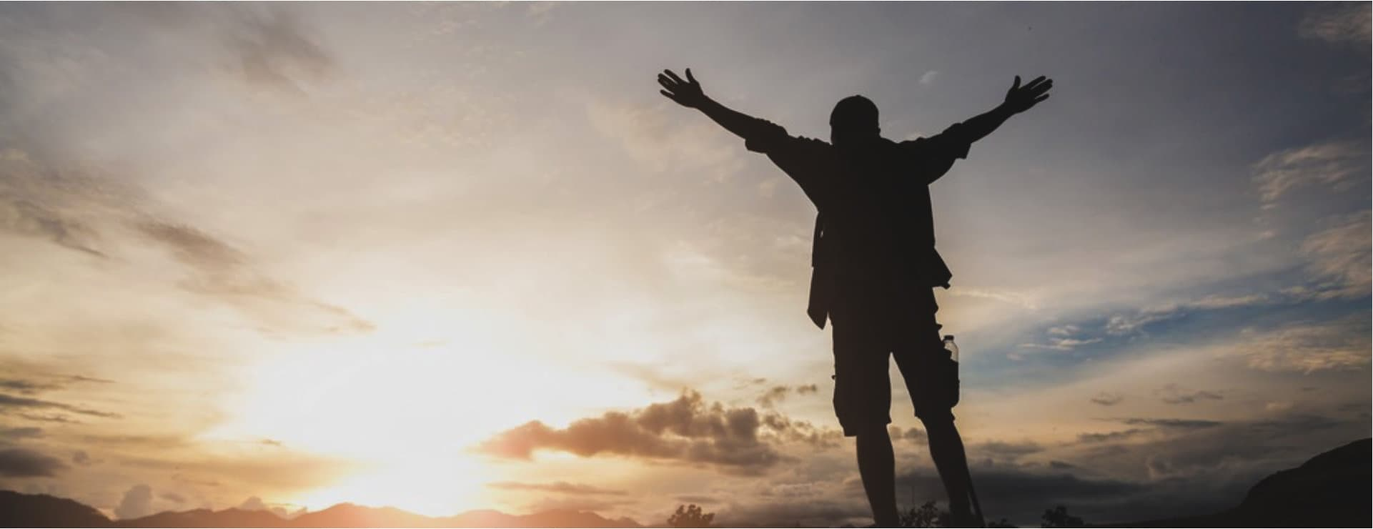 man facing sunrise with arms wide open