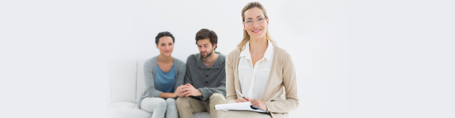 happy therapist with couple on her background
